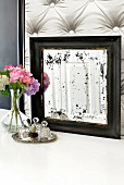 Old mirror with spots, vase of hydrangeas and small perfume bottles on silver tray