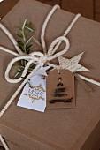 Ein Geschenk in Kraftpapier mit weißer Kordel und gebastelten Etiketten