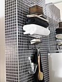 Stacked towels on top of wall-mounted shelves with hooks below on grey mosaic-tiled wall