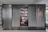Bookcases hidden in grey cubic installation in modern interior