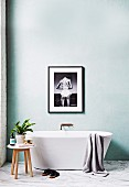 Striking black and white photo of a freestanding bathtub on a marble floor