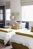 Zwei Einzelbetten mit Volants und Zierkissen im Gästezimmer mit limettenfarbenen Akzenten