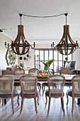 Vintage cane-back chairs around dining table below two large wood-and-metal chandeliers