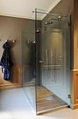 Doppeldusche mit moderner Glasabtrennung und Holzboden im Bad mit traditioneller Kassettenverkleidung und Fliesenboden