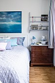 Structured bedspread on bed with headboard and rustic wash basin and pitcher on bedside cabinet in corner of bedroom