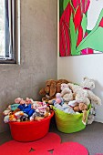 Colorful plastic tubs with soft toys in children's corner with concrete wall and modern picture