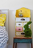Yellow vintage drawer case with various patterns and green rabbit figure on rustic bedside table in children's room