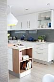 White, glossy modern kitchen with glass splashbacks and island counter