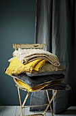 Alter Gartenstuhl mit einem Stapel aus Kissen und Leinentüchern in Blau und Gelb