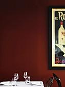Gedeckter Tisch mit Wein- und Wassergläsern vor dunkelroter Wand mit Retro-Werbeplakat