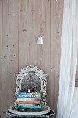 Shabby-chic chair with ornate backrest against board wall