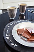 Squares of chocolate on plate on chalkboard charger plate with writing around rim
