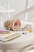 Jewellery spilling out of small, hand-crocheted bag lined in pink