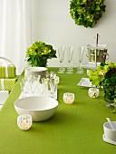 Geschirrstapel, Gläser und Windlichter auf grün gedecktem Tisch mit Blumendekoration