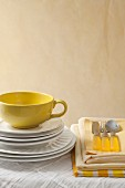 Stacked white plates, yellow cup, table linen and cutlery