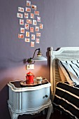 Antikes Nachtkästchen und Vintage Wandleuchte an mauvefarbener Wand mit Fotos im Schlafzimmer