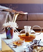 Glass teapot and glass teacup on coffee table