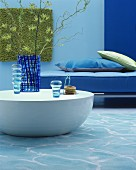 Blue glass vases on sold round coffee table in front of blue sofa