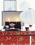 Modern table lamp on lacquered cabinet; white lanterns