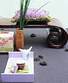 Tea service on modern tray in front of Oriental bench with spiral legs