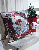 Embroidered cushion with dog motif, miniature tree and bauble on white, shabby-chic bench