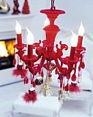 Roter Kronleuchter mit verschiedenen Motiv-Anhängern dekoriert