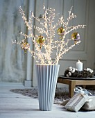Christmas baubles hung from white, artificial branches in vintage interior