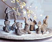 Various terracotta cherubs amongst artificial snow on plate