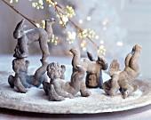 Verschiedene Terracotta-Putten auf Teller mit Kunstschnee