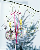 Christmas-tree candle clipped to wire coat hanger and baubles hanging from bare branch