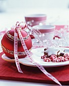 Red bauble with white pattern and white ribbon with red lettering decorating dining table