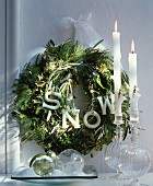 Green wreath with decorative letters and white ribbon behind glass baubles and white candles in elegant glass candlesticks