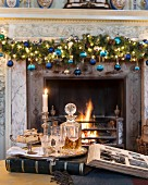 Carafe of whisky and glasses on tray in front of festive fireplace