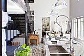 Modern stainless steel kitchen and metal staircase in loft apartment