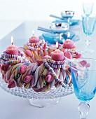 Adventskranz aus Süssigkeiten, mit Brauseketten und brennenden rosafarbenen Kerzen