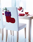 Felt Christmas stocking on backrest of white chair