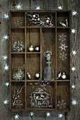 Christmas decorations in old wooden display case surrounded by star-shaped fairy lights