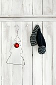 Wire coat hanger bent into Christmas tree shape and bobble hat hung on white-painted board wall