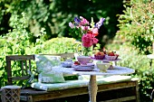 Wooden bench and table set with vase of flowers in summery garden