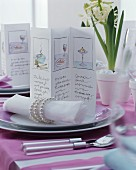 Pictures on menu cards and linen napkins with elegant napkin rings on festively set table