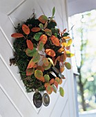 Autumnal moss door wreath decorated with colourful leaves