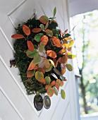 Herbstlicher Türkranz aus Moos mit bunten Blättern