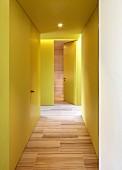 Yellow hallway with wood-effect tiled floor