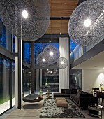 Enormous spherical lampshades and suspended fireplace in double-height, futuristic living room