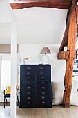 Black chest of drawers below rustic wooden beams