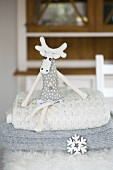 Fabric moose sat on stack of woollen blankets