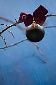 Schwarze Christbaumkugel mit einer Schleife aus Filz am Zweig