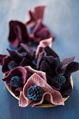 Blue-painted larch cones in folds of felt in berry shades
