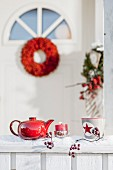 Teapot, candle and cup on snowy veranda balustrade with front door in background