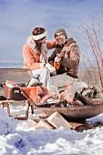 Frau und Mann mit Gitarre beim Winter-Picknick in verschneiter Landschaft